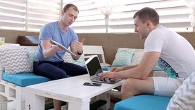 Men work with tablets in a cafe. Two men met in a cafe to discuss matters stock video