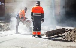 Men at work, urban road under construction. Saint-Petersburg, Russia - May 32, 2015: men at work, urban road under construction, sawing of a roadside border royalty free stock image