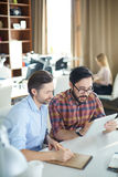 Men at work. Young men presenting and explaining financial data to his colleague Royalty Free Stock Photography