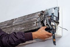 Cleaning electrician air conditioner. Men worker cleaning electrician air conditioner dirty in home stock photography