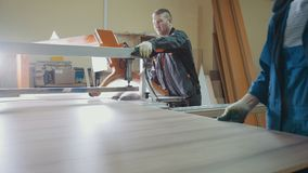 Men workers at factory are cutting wooden fragment on electric saw at furniture industry. Wide view Stock Photography