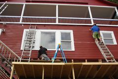 Men Working. Two men painting a red house on a platform Stock Images