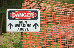 Men working above sign. A sign on the edge of a construction site that says: Danger men working above Stock Photography