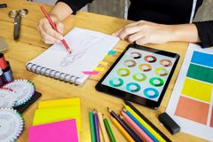 Men working as fashion designer choosing on colour chart for clo. Women working as fashion designer choosing on colour chart for clothes in digital tablet at Royalty Free Stock Photo