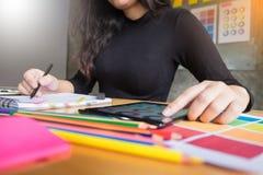 Men working as fashion designer choosing on colour chart for clo. Women working as fashion designer choosing on colour chart for clothes in digital tablet at Stock Image