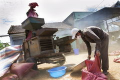 Men working on coffee beans sorting machine on street on February 11, 2012 in Nam Ban, Vietnam. NAM BAN, VIETNAM - FEBRUARY 11: Men working on coffee beans royalty free stock photo