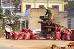 Men working on coffee beans sorting machine on street on February 11, 2012 in Nam Ban, Vietnam. NAM BAN, VIETNAM - FEBRUARY 11: Men working on coffee beans royalty free stock images
