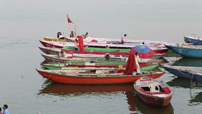 Men working on colorful boats in bay of Ganges river in Varanasi. stock footage