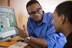 Men working at computer. Instructor discussing work at a computer monitor Stock Photo