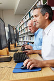 Men working on computers in library Royalty Free Stock Images