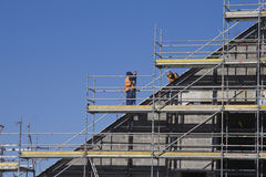 Men working at construction site. Men working at the new construction site with blue sky on background Stock Image