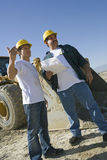 Men Working At Construction Site. Two workers in helmet working at construction site Royalty Free Stock Photography