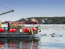 Men working on crab boat. A crab boat with crabbers and traps working the ocean in Southern British Columbia Stock Photo