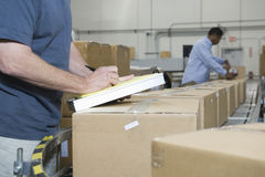 Men Working In Distribution Warehouse. Closeup of a cropped men writing with worker in background at distribution warehouse stock image