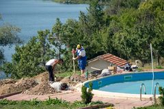 Men working on the in-ground swimming pool. Workers built a swimming pool in resort in Pchelina Dam, Bulgaria Stock Photos