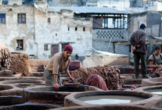 Men working hard in the tannery souk in Fez, Morocco. FEZ, MOROCCO - JANUARY 4, 2014: Man working hard in the tannery souk in Fez, Morocco. The tannery souk of Stock Image
