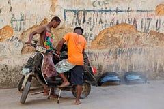 Men working on motorcycle - Zanzibar Stock Photography