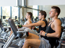 Men working out on exercise bike in gym Royalty Free Stock Photos