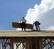 Men working on roof top Stock Images