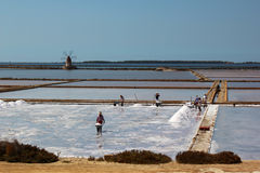 Men working on the saltpans in Mozia in Sicily Royalty Free Stock Photos