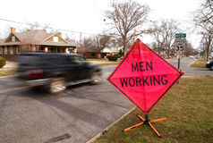 Men working sign. A men working sign by a busy street stock images