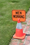Men Working sign. A small Men Working sign on an orange cone on a brick walkway by a lawn Royalty Free Stock Images