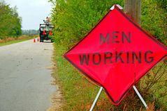 Men Working Sign and Workers. Roadside men working sign with truck and workers in background Royalty Free Stock Images