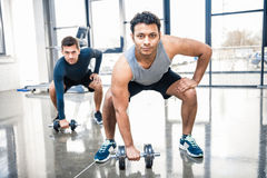 Men workout with dumbbells at gym. Young men workout with dumbbells at gym royalty free stock photo