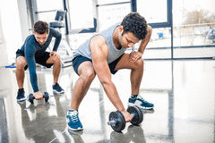 Men workout with dumbbells at gym. Young men workout with dumbbells at gym royalty free stock photos