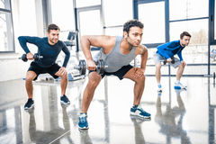 Men workout with dumbbells at gym. Young men workout with dumbbells at gym stock image