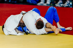 Men wrestlers judoka. White and blue kimono on tatami fight choke hold with legs Stock Photo