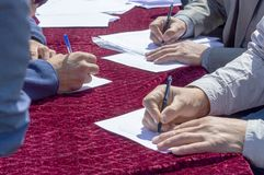 Men write with pens on the book on the table. Top side view stock photo