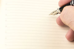 Men is writing with ink pen into the blank notebook with lines Stock Image