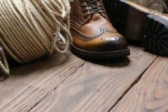 Men& x27; ботинки s, веревочка джута мотка на предпосылке деревянных доск Стоковое фото RF