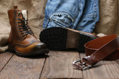 Men& x27; ботинки s, джинсы, кожаный пояс на предпосылке деревянной планки Стоковые Изображения RF