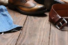 Men& x27; ботинки s, джинсы, кожаный пояс на предпосылке деревянной планки Стоковые Изображения