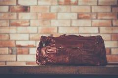 Men& x27; accesorios de s con los bolsos de cuero marrón oscuro en la tabla de madera o Imágenes de archivo libres de regalías