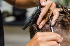 Men& x27; el corte del pelo de s scissors en un salón de belleza Fotografía de archivo libre de regalías