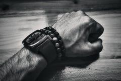 Men& x27; s brutalna ręka dekoracyjne bransoletki i zegar Obraz Stock