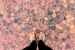 Men& x27; s-Füße auf einer alten sechseckigen Fliese Stockbild