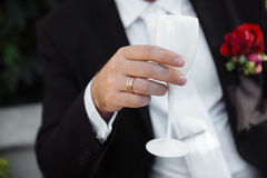 Men's hand with white glass and gold ring Stock Photos