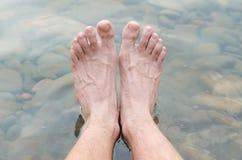 Men& x27;s legs in fresh water, mountain river. Stock Photos