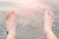 Men& x27;s legs in fresh water, mountain river. Royalty Free Stock Image