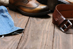 Men's shoes, jeans, leather belt on a background of wooden plank Stock Images