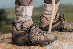 Men's Brown and Gray Merrell Hiking Shoes Holding Stick Royalty Free Stock Photo