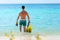 Men in yellow mask and flippers going snorkeling Stock Images