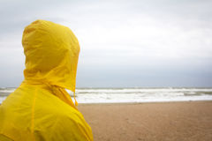Men in yellow raincoat on the beach looking at storm. Stock Photography