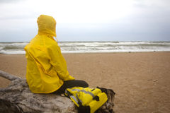 Men in yellow raincoat on the beach looking at storm. Stock Photo
