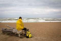 Men in yellow raincoat on the beach looking at storm. Royalty Free Stock Photos