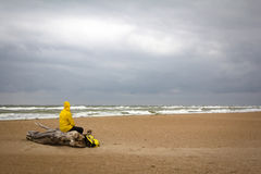 Men in yellow raincoat on the beach looking at storm. Stock Image